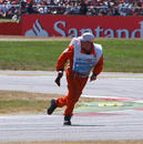 A marshal sprints clear after picking up debris from the track