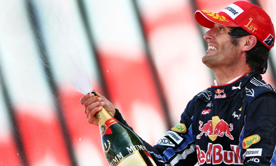 Mark Webber sprays the champagne on the podium