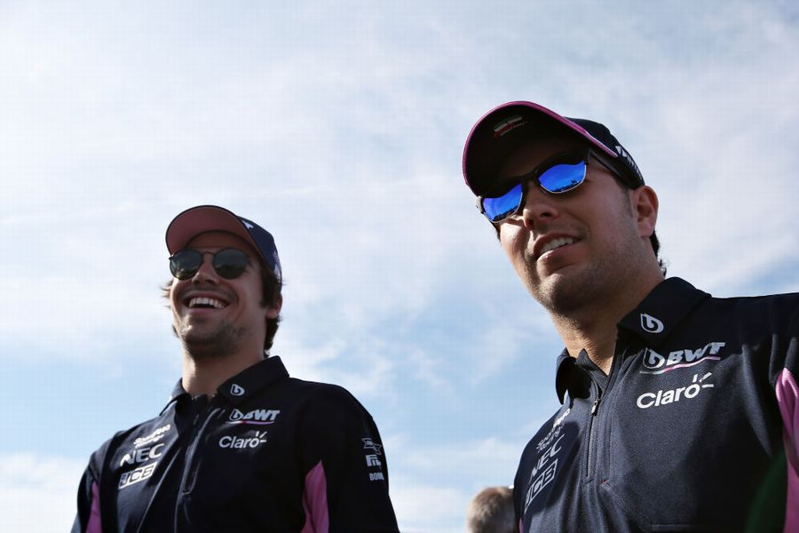 Sergio Perez and Lance Stroll smile in the Paddock