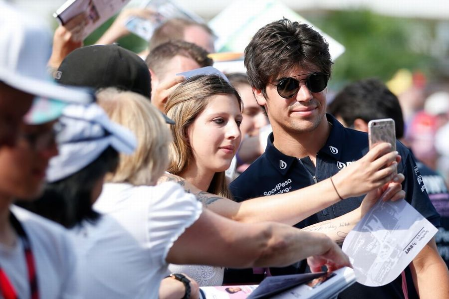 Lance Stroll poses for a photo with fans