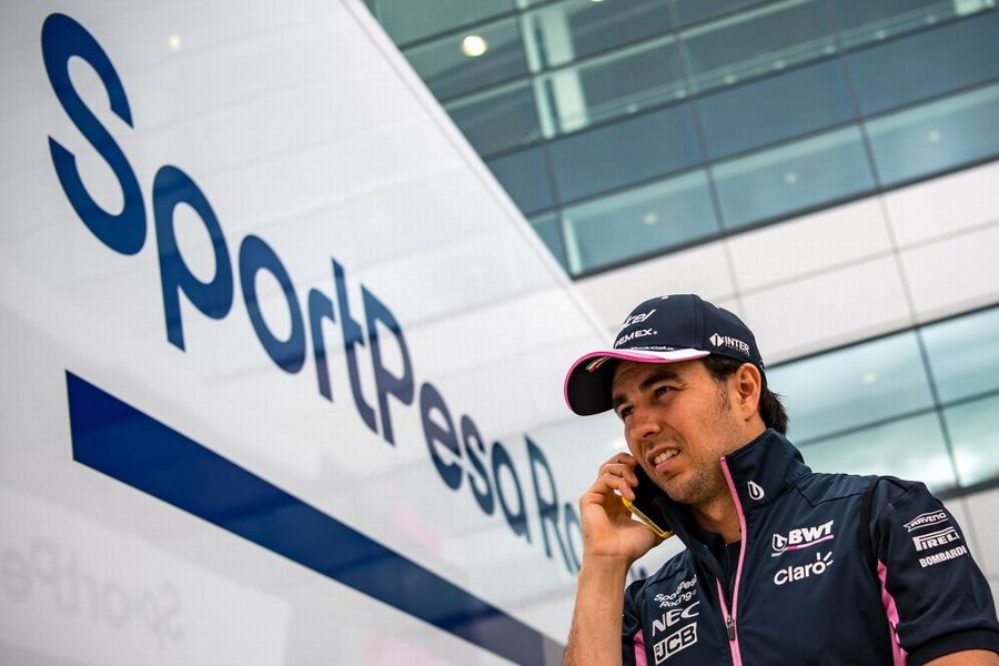 Sergio Perez speaks on his cell phone in the paddock