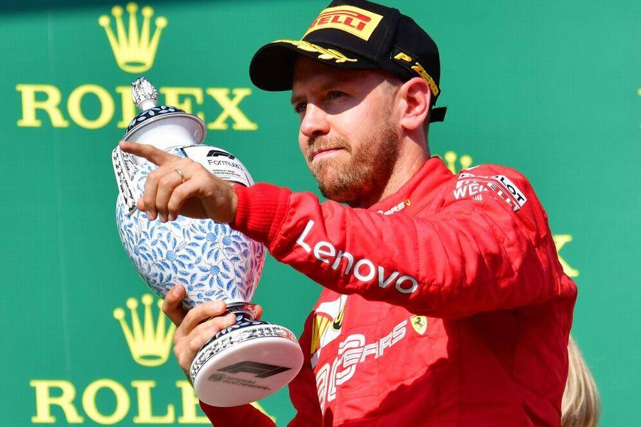 Sebastian Vettel celebrate on the podium with the trophy