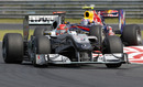Michael Schumacher keeps an eye on his mirrors as Mark Webber closes in