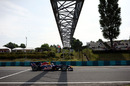 Sebastian Vettel flashes under the bridge