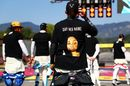 Lewis Hamilton wears a t-shirt displaying the message 'say her name' above a photo of Breonna Taylor