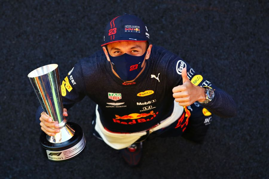 Alexander Albon celebrates on the podium with the trophy