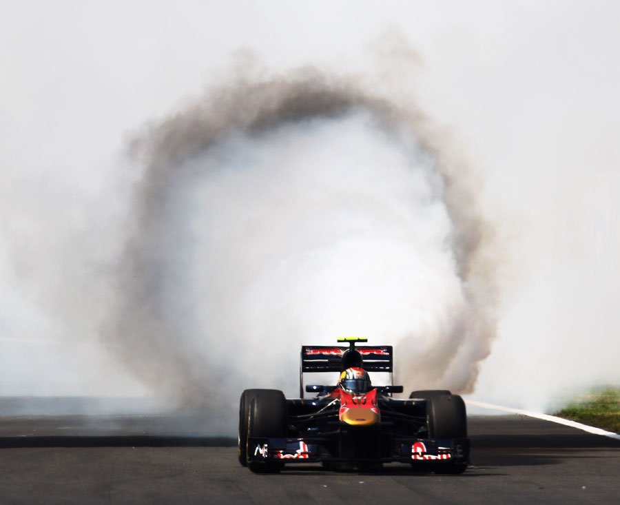 Smoke billows from the back of Jaime Alguersuari's Toro Rosso at the start