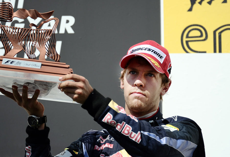 A disappointed Sebastian Vettel with his trophy for third place