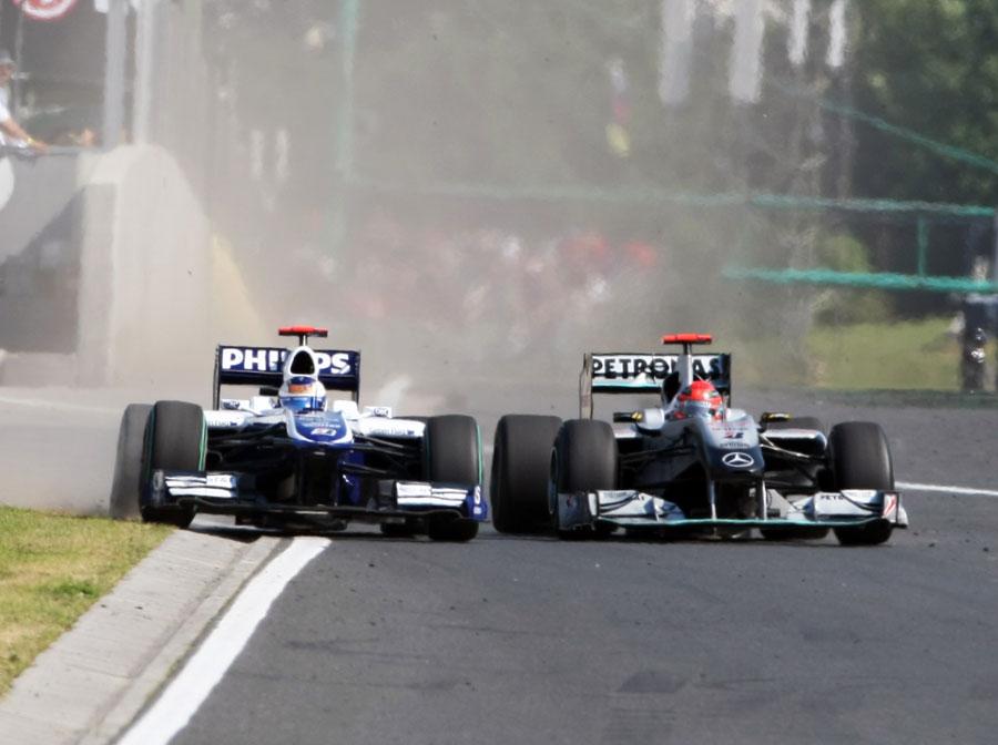 Michael Schumacher squeezes Rubens Barrichello off the circuit