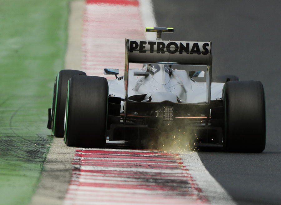 Nico Rosberg rides the kerb on the exit