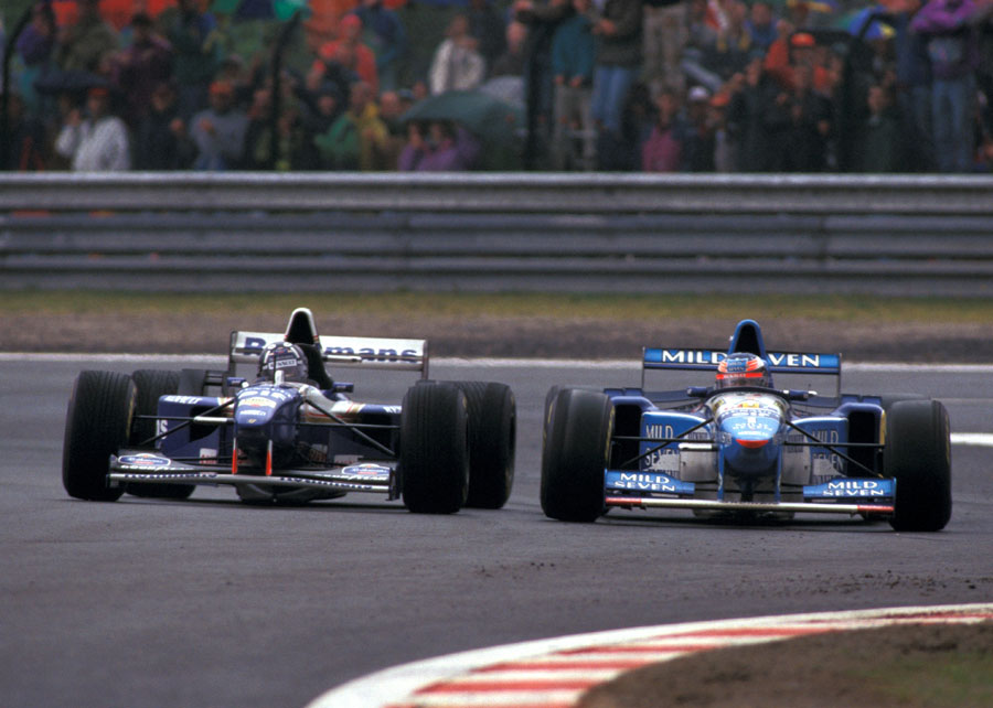 Michael Schumacher (on slicks) holds off Damon Hill in damp conditions