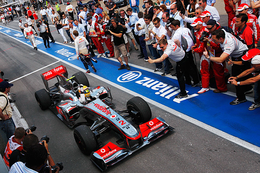 Lewis Hamilton celebrates victory on his return to the pits