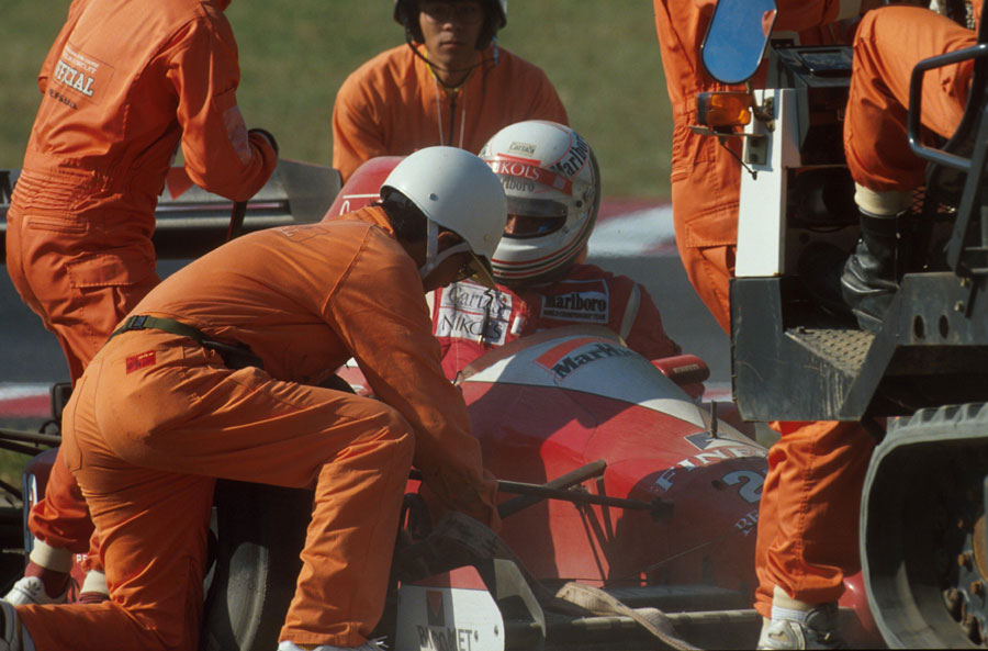 Marshals get to work after Andrea de Cesaris crashes out of the Japanese GP