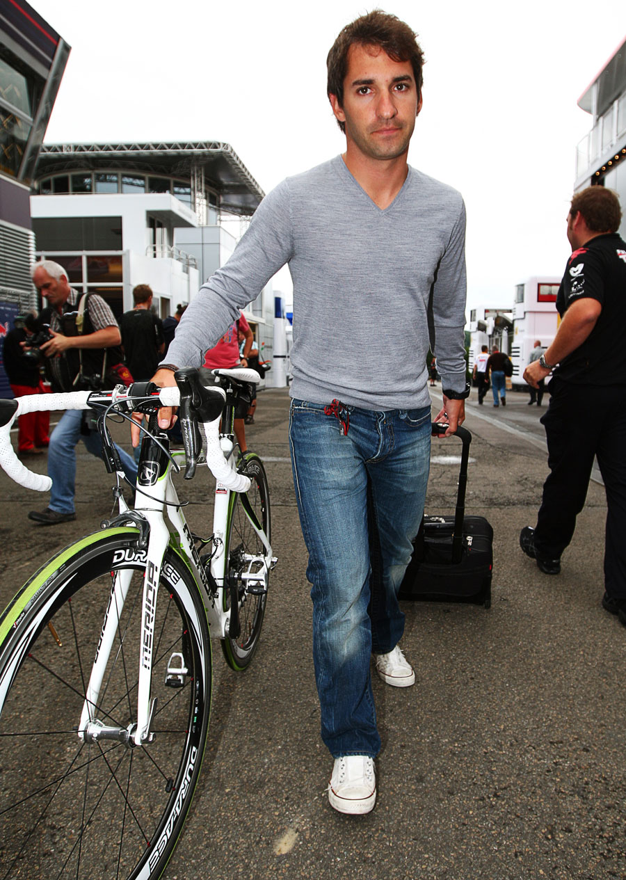 Timo Glock arrives in the paddock with his bike and suitcase in tow