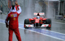 Fernando Alonso returns to the pits amidst torrential rain