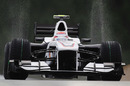 Kamui Kobayashi's tyres throw up an arc of water