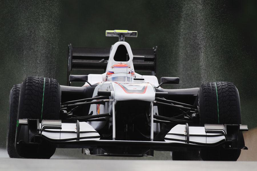 Kamui Kobayashi's tyres throw up an arc of water