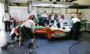 Force India mechanics work on the car of JR Hildebrand in the team gararge