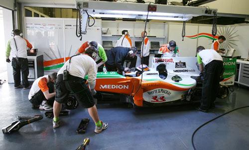 Force India mechanics work on the car of JR Hildebrand in the team gararge
