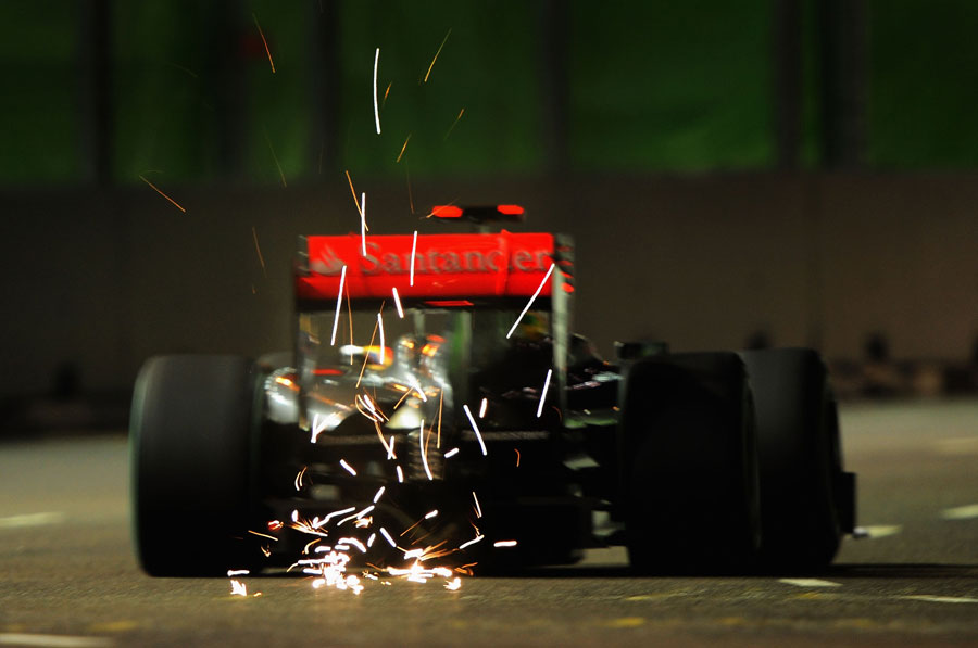 Sparks fly from the back of Lewis Hamilton's McLaren