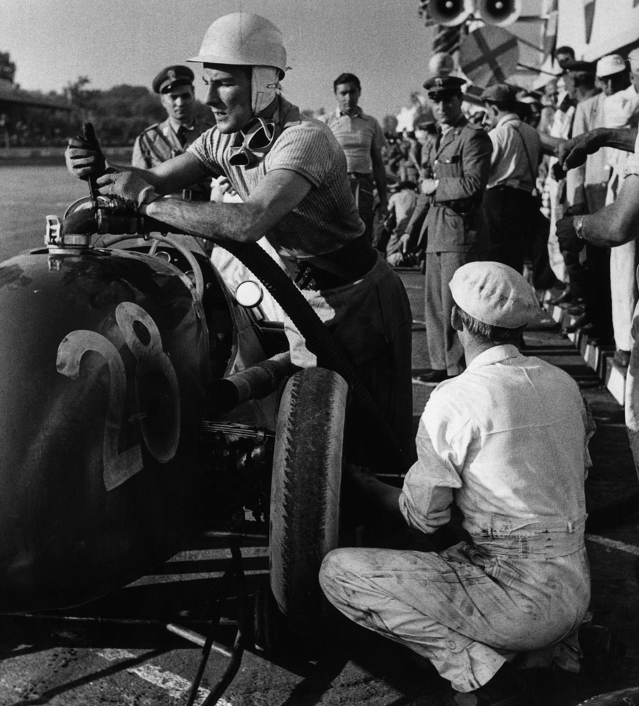 Stirling Moss fills his car with fuel during a pit stop