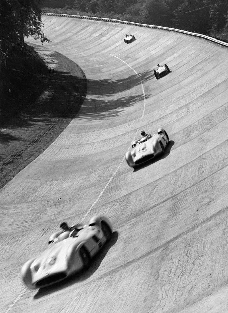 The streamline Mercedes of Juan Manuel Fangio and Stirling Moss lead the field through the banking