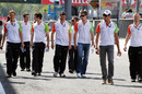Adrian Sutil and Paul di Resta walk down the pit lane