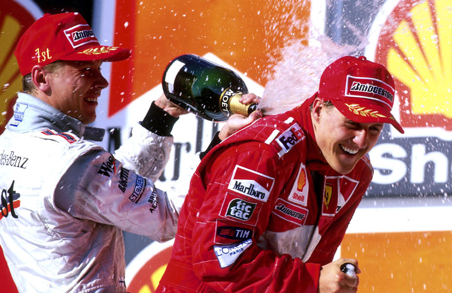 Mika Hakkinen sprays Michael Schumacher with champagne