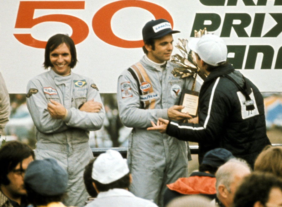Emerson Fittipaldi looks on as Peter Revson is presented with the trophy