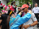 Lewis Hamilton is garlanded by a woman in traditional Chinese dress