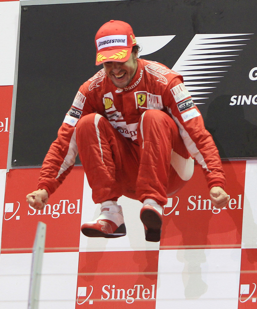 Fernando Alonso leaps in the air to celebrate his victory