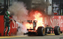Heikki Kovalainen tries to put out an engine fire