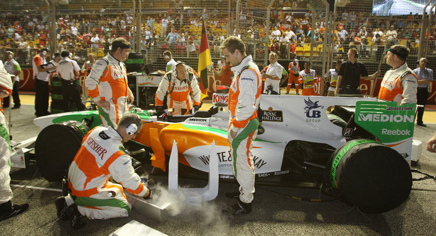 Adrian Sutil looks on as his car is prepared