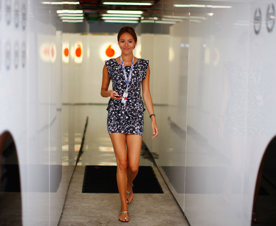 Jenson Button's girlfriend Jessica Michibata walks out of the McLaren garage