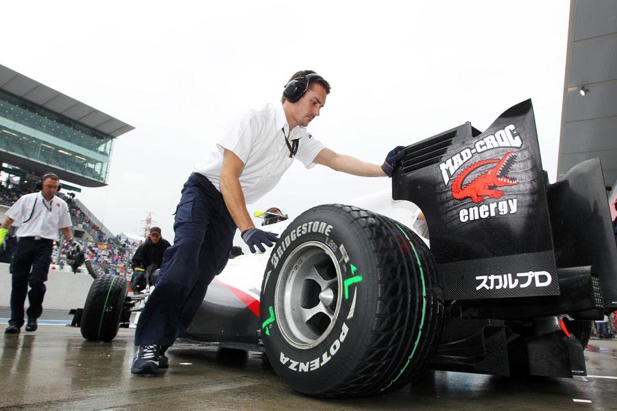 Kamui Kobayashi's Sauber is pushed back into the garage