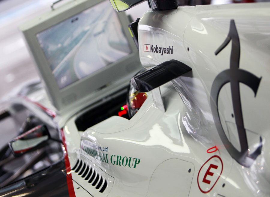 Kamui Kobayashi watches a soaking wet practice session from the garage