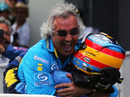 Flavio Briatore celebrates with Fernando Alonso after Renault's win at the 2005 European Grand Prix