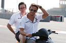 Jenson Button and race engineer Andy Shovlin ride a moped around Yas Marina