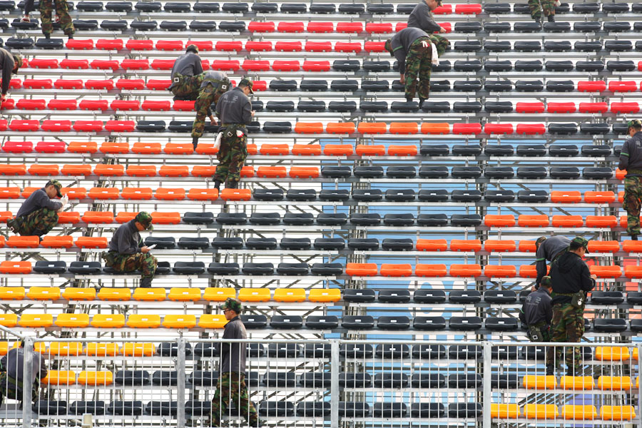Workmen fill the grandstands with seats
