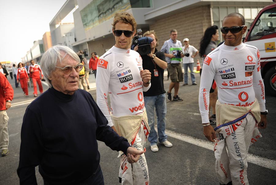 Bernie Ecclestone walks with Jenson Button and Lewis Hamilton