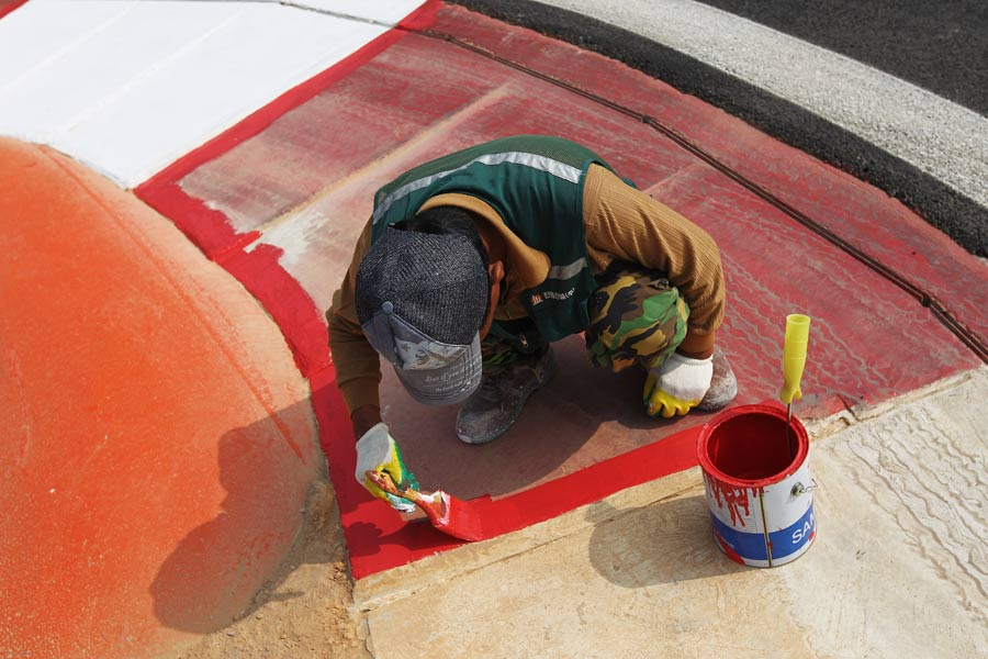 A worker finishes painting the kerbing