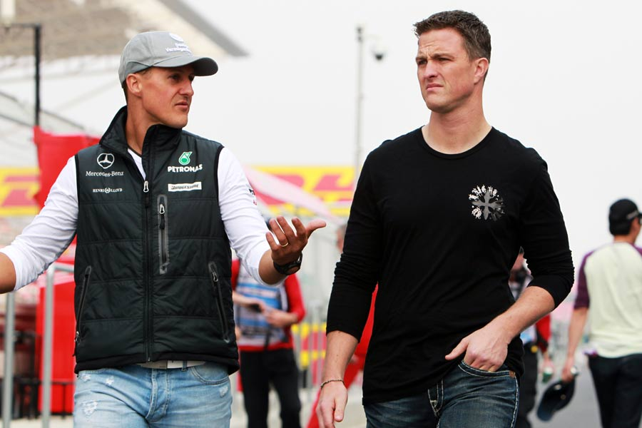 Michael Schumacher chats to brother Ralf in the paddock