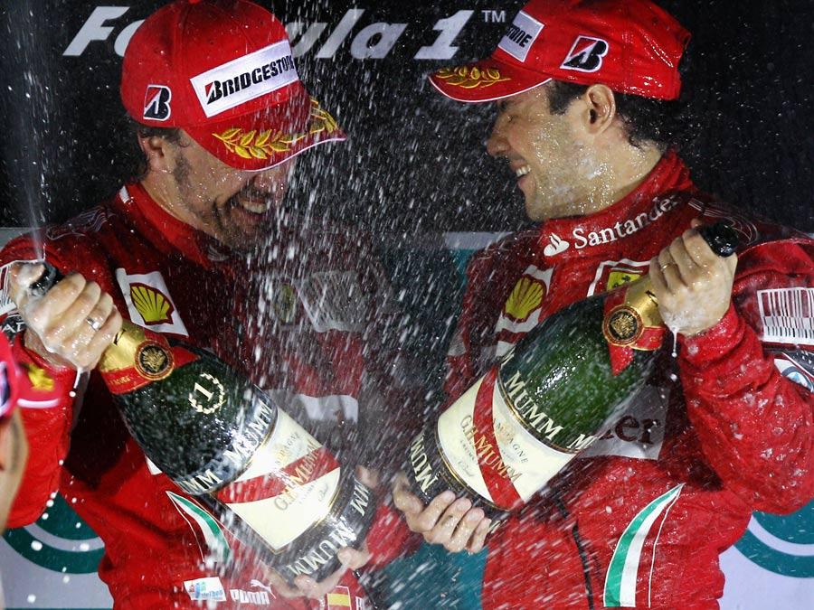 Fernando Alonso and Felipe Massa celebrate on the podium