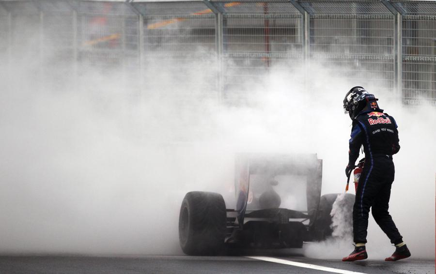 Sebastian Vettel abandons his smouldering Red Bull