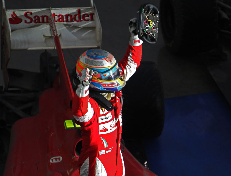 Fernando Alonso celebrates on top of his Ferrari