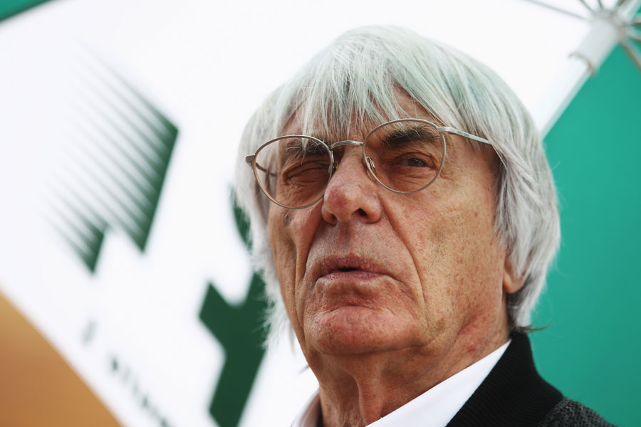 Bernie Ecclestone shelters  from the rain