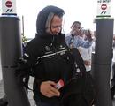 Michael Schumacher arrives in the paddock wearing his rain coat