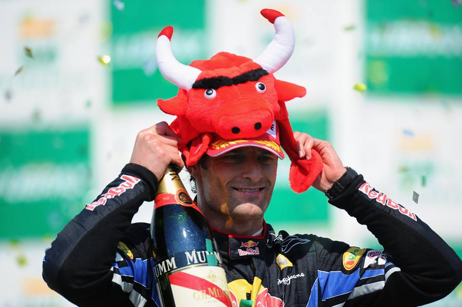 Mark Webber tries on a Red Bull hat