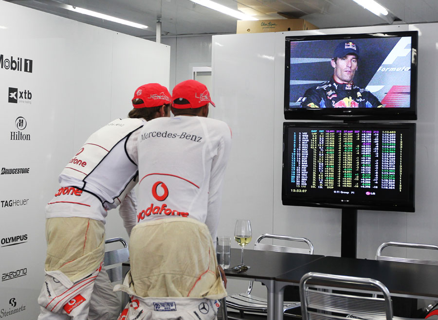 Jenson Button and Lewis Hamilton watch the press conference