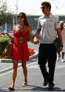 Jessica Michibata leads boyfriend Jenson Button through the paddock